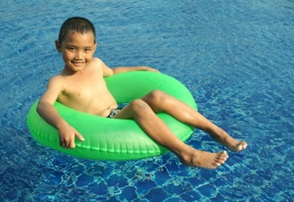 boy floating swim ring Summer Safety Tips for Kids