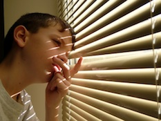 child looking out blinds Top Tips to Keeping Your Kids Safe When Home Alone