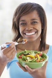 Teenage Girl Holding A Bowl Of Salad And Smiling At The Camera
